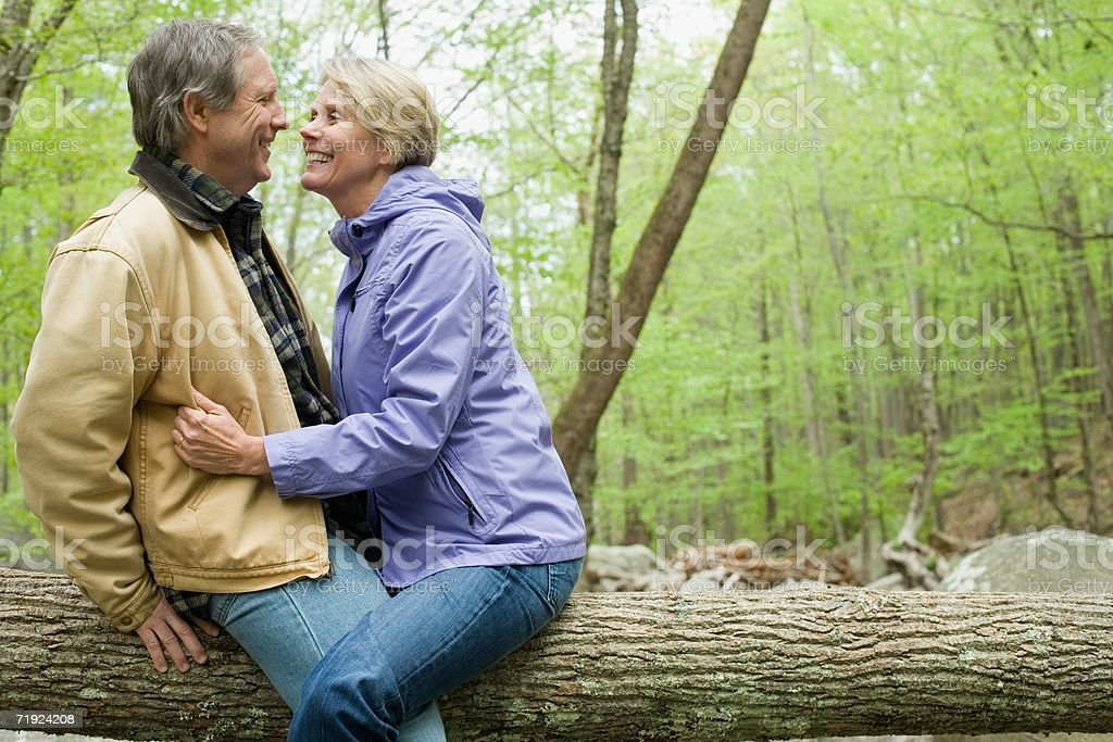 Mature couple hugging on a log royalty-free stock photo