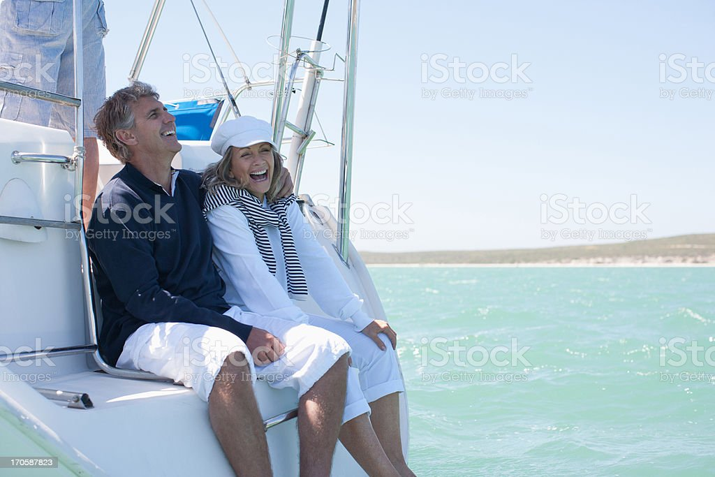 Mature couple hugging on deck of sailboat stock photo