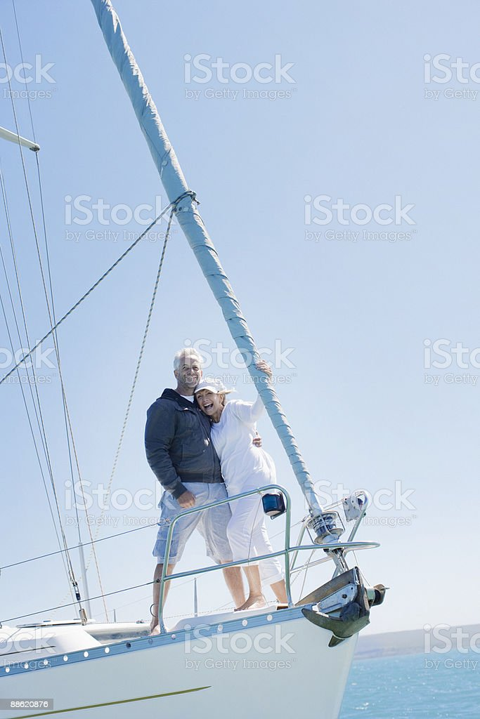 Mature couple hugging on deck of sailboat royalty-free stock photo