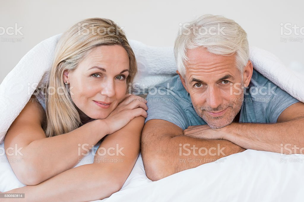 Mature couple in bed stock photo