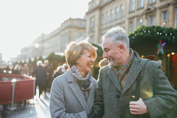 Mature Couple In Christmas Market A mature married couple are walking through a Christmas market together. christmas fun stock pictures, royalty-free photos & images