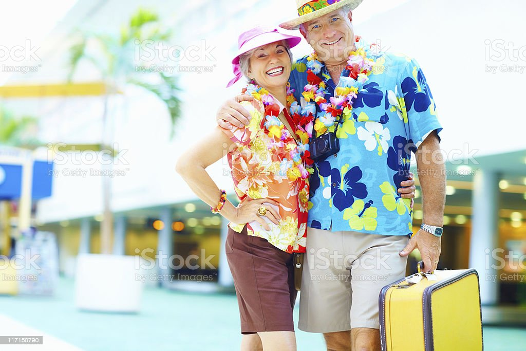 Mature couple in floral clothing with luggage at an airport royalty-free stock photo