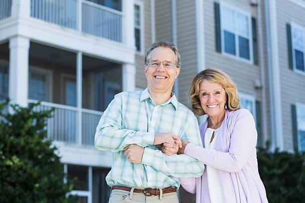älteres paar vor apartment-gebäude - seniorenwohnungen stock-fotos und bilder
