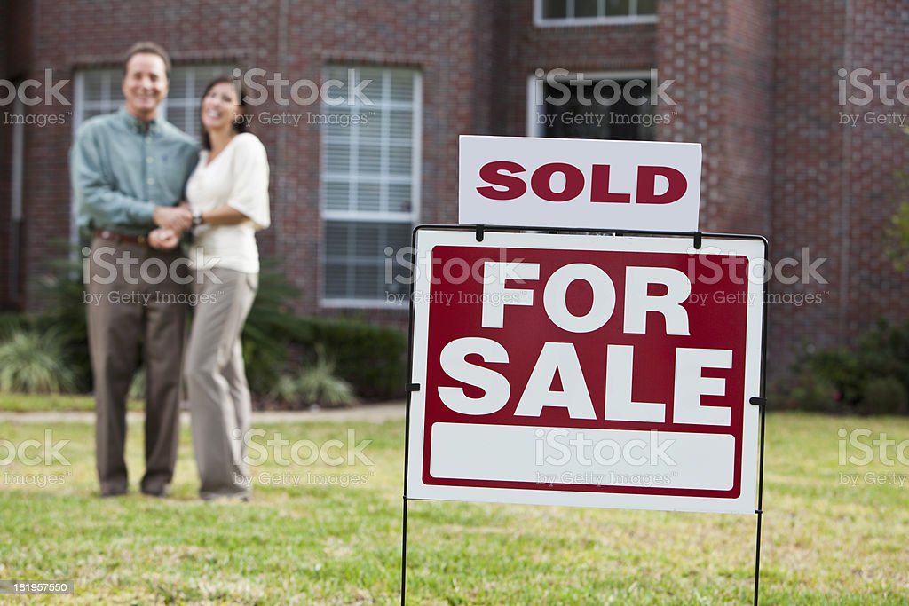 Mature couple in front of house with SOLD sign royalty-free stock photo