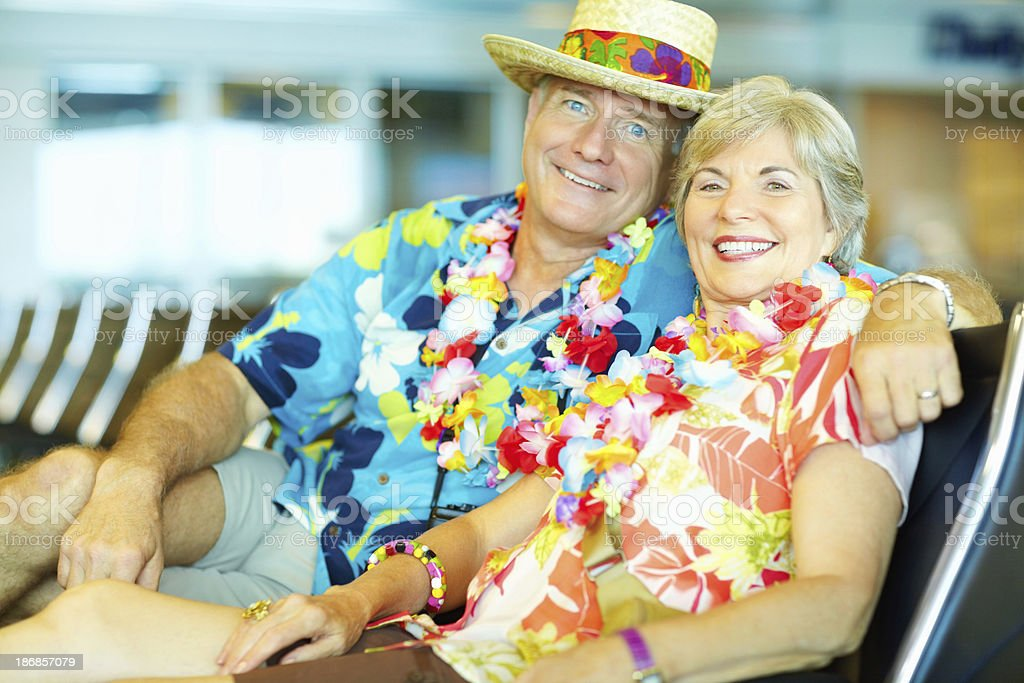Mature couple in Hawaiian clothing at an airport lounge royalty-free stock photo