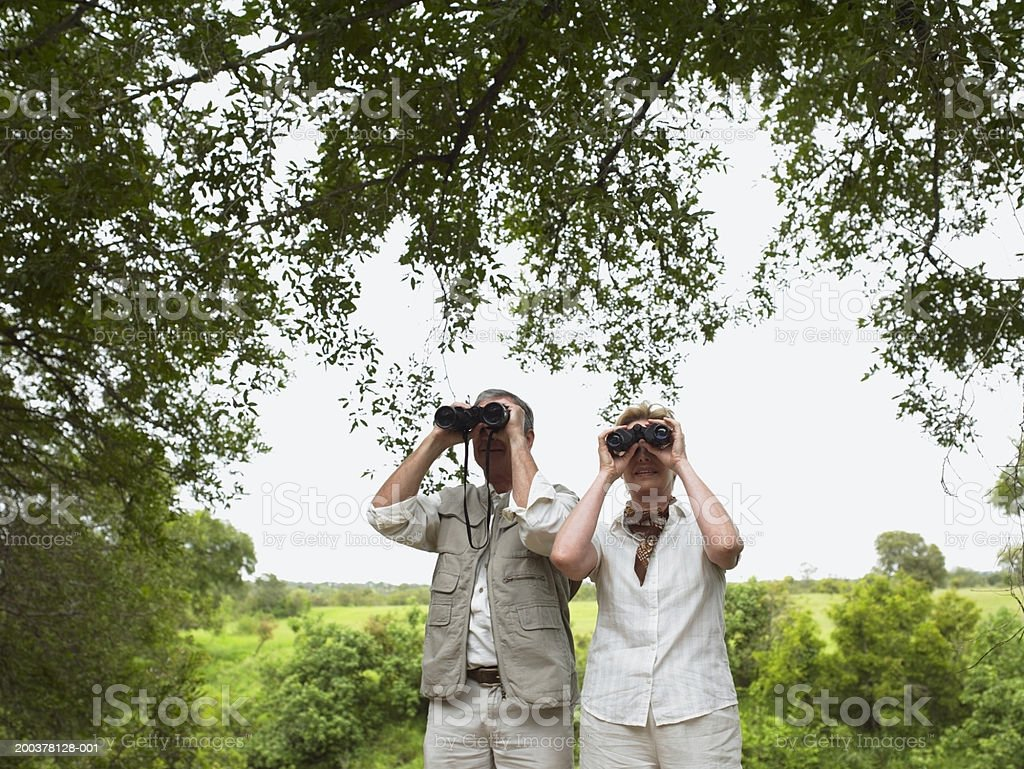 Mature couple in landscape using binoculars stock photo