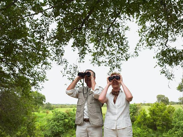 Mature couple in landscape using binoculars stock photo