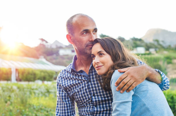 Mature couple in love Loving man and happy woman in a spring blooming park. Happy mature couple in love embracing outdoor. Hispanic boyfriend embracing her brunette girlfriend during sunset in a summer day. husband stock pictures, royalty-free photos & images