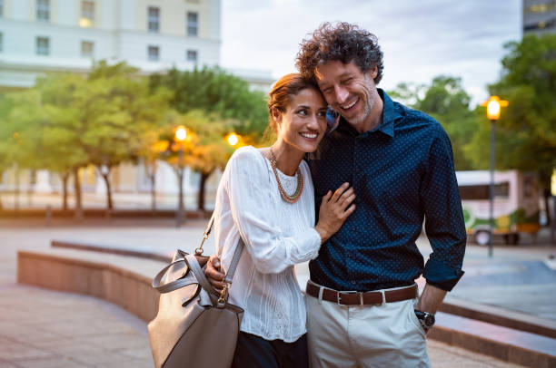 Mature couple in love walking in street Romantic mature couple enjoying evening walk after office. Cheerful man and beautiful woman embracing while walking on city streets. Handsome man and woman spending evening together outdoors. mature couple stock pictures, royalty-free photos & images