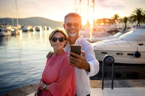 reife paar in port machen foto mit smartphone - senior bilder wasser stock-fotos und bilder