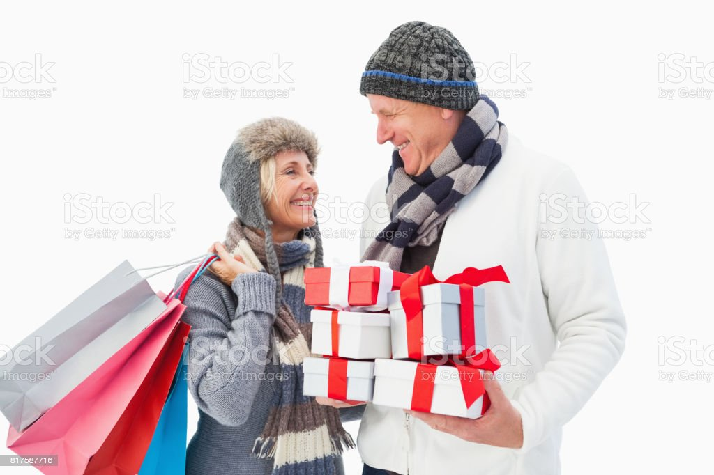 Mature couple in winter clothes holding gifts stock photo