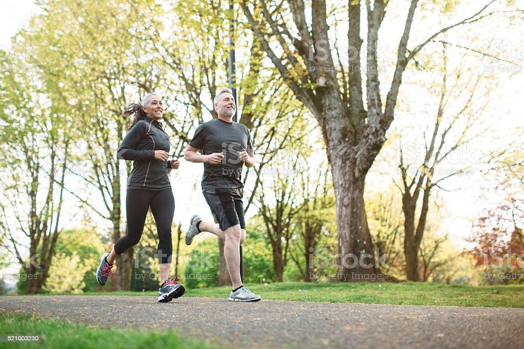 Mature Couple Jogging Outdoors stock photo