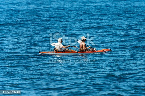 Gulf of La Spezia, Liguria, Italy - July 21th, 2019: a mature couple aboard an orange kayak, paddling in the blue Mediterranean sea, Gulf of La Spezia, Liguria, Italy, Europe