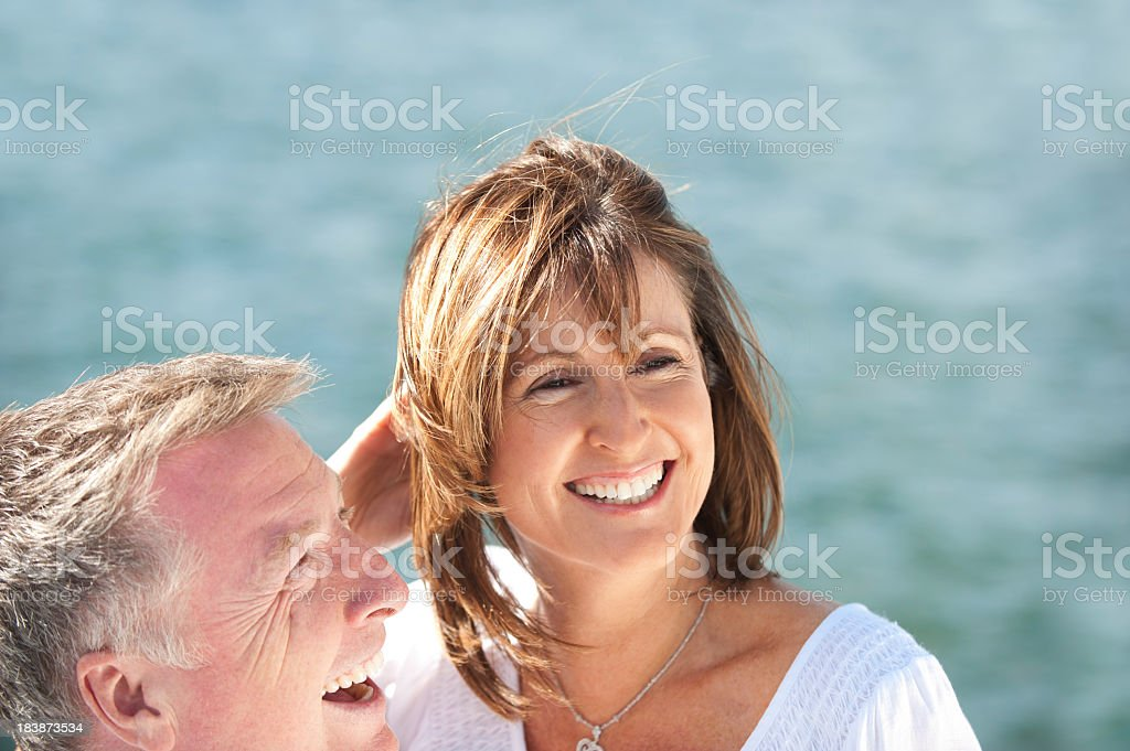 Mature couple laughing with water background