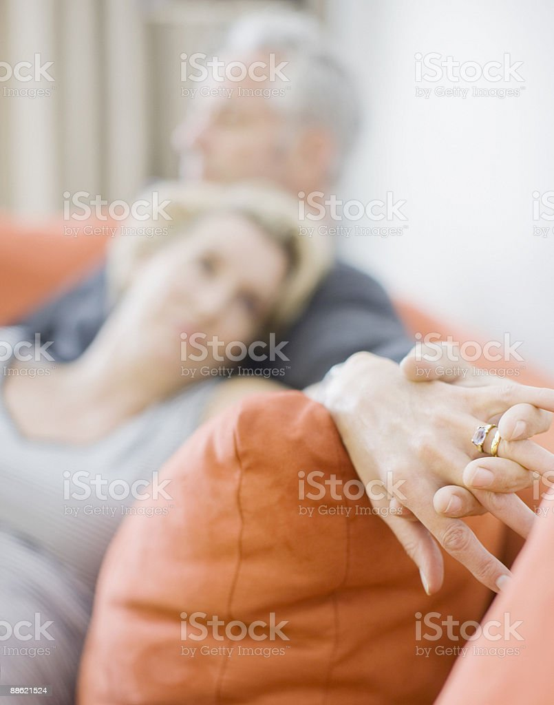 Mature couple laying on sofa holding hands royalty-free stock photo