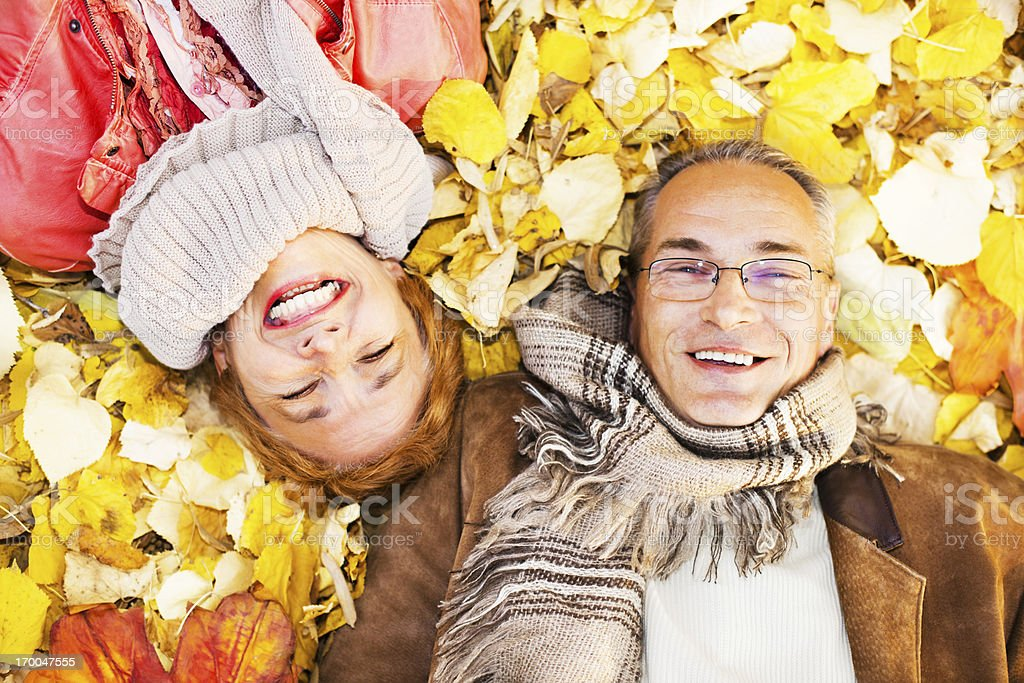 Mature couple lying among the leaves. royalty-free stock photo