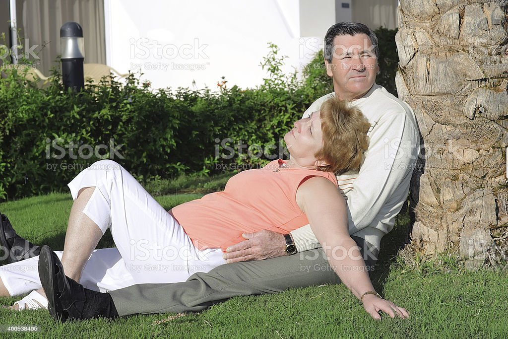 Mature couple lying in embrace near palm-tree. royalty-free stock photo