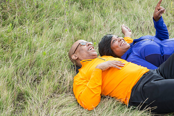 Mature couple lying on backs in park looking at sky stock photo