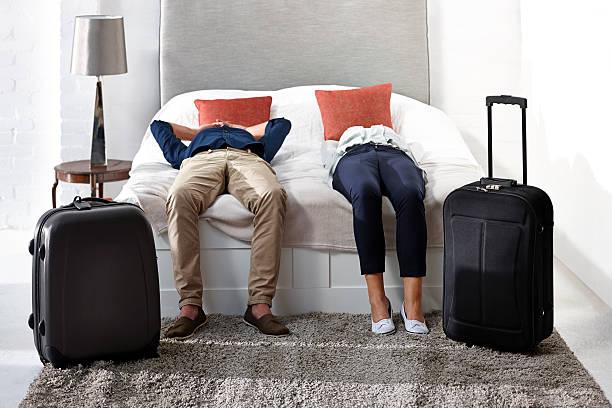 pareja madura yacer en la cama con su equipaje - llegada fotografías e imágenes de stock