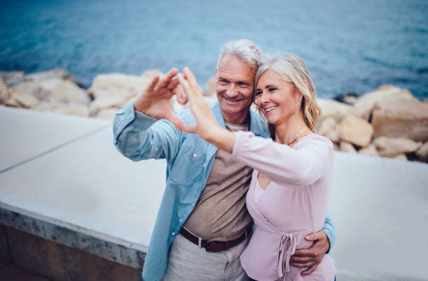 mature couple making heart shape with their hands at seaside - senior valentine stock photos and pictures
