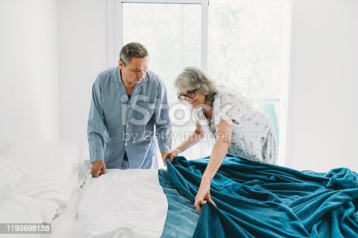 Mature couple making the bed together. They are helping each other. They are wearing pajamas and just woke up.