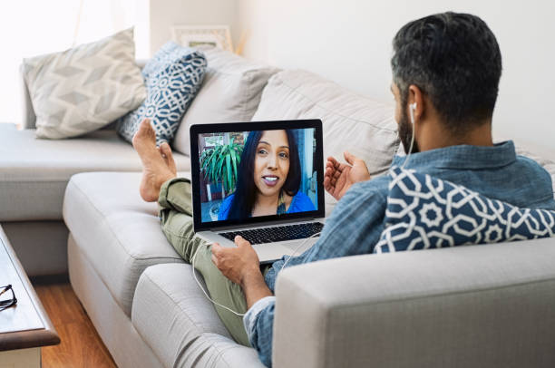Mature couple making video call Rear view of husband relaxing on couch while talking to his wife using laptop at home. Mature man lying on sofa and indian woman communicate through video chat on laptop. Smiling couple talking through video call on laptop. long distance relationship stock pictures, royalty-free photos & images