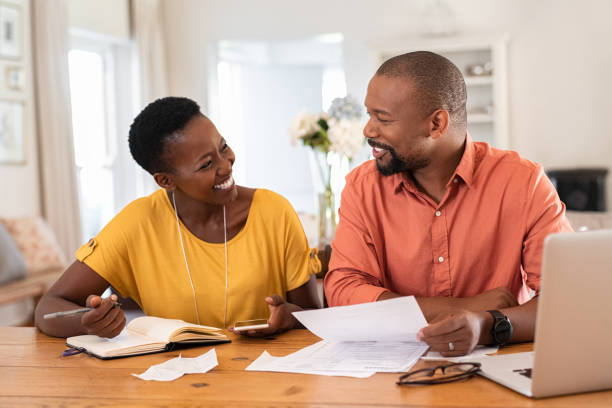 Mature couple managing home finance Cheerful mature couple sitting and managing expenses at home. Happy african man and woman paying bills together and managing budget. Black smiling couple checking accountancy and bills while looking at each other. face to face stock pictures, royalty-free photos & images