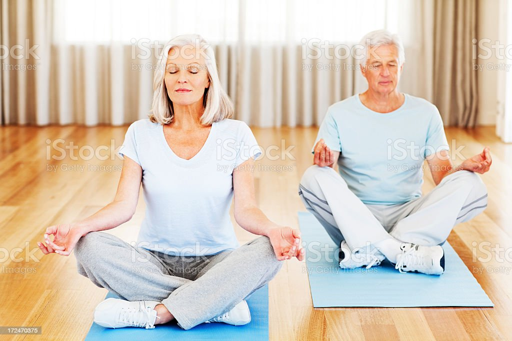 Mature couple meditating on wood floor royalty-free stock photo