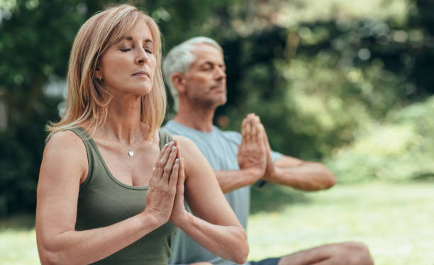 Mature couple meditating together during yoga practice outside stock photo
