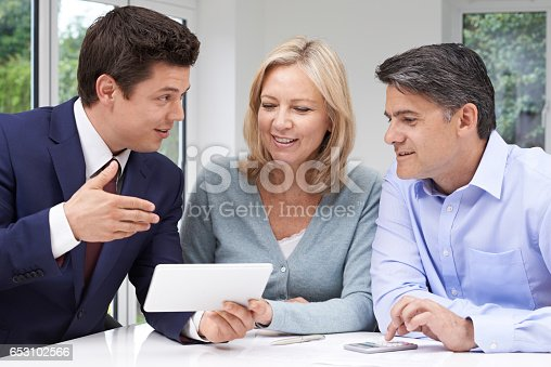 istock Mature Couple Meeting With Financial Advisor At Home 653102566