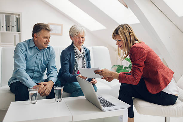 Mature Couple Meeting with Financial Advisor. Mature Couple Meeting with Financial Advisor. They are listening to financial advisor. She is speaking about retirement and insurance options for them. Holding contract in her hands and explaining to clients. mortgages and loans stock pictures, royalty-free photos & images