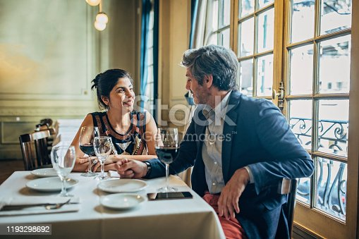 Man and woman, modern heterosexual couple sitting in restaurant on a date.