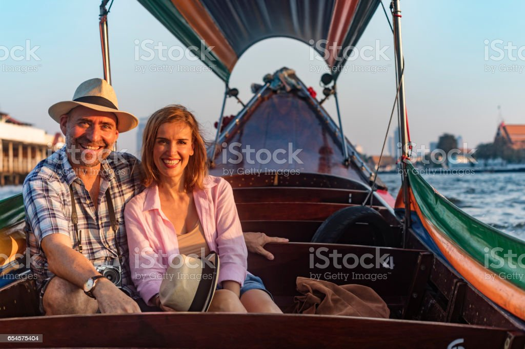 Mature Couple on a Romantic Sunset Boat Cruise on the River in Bangkok Thailand stock photo