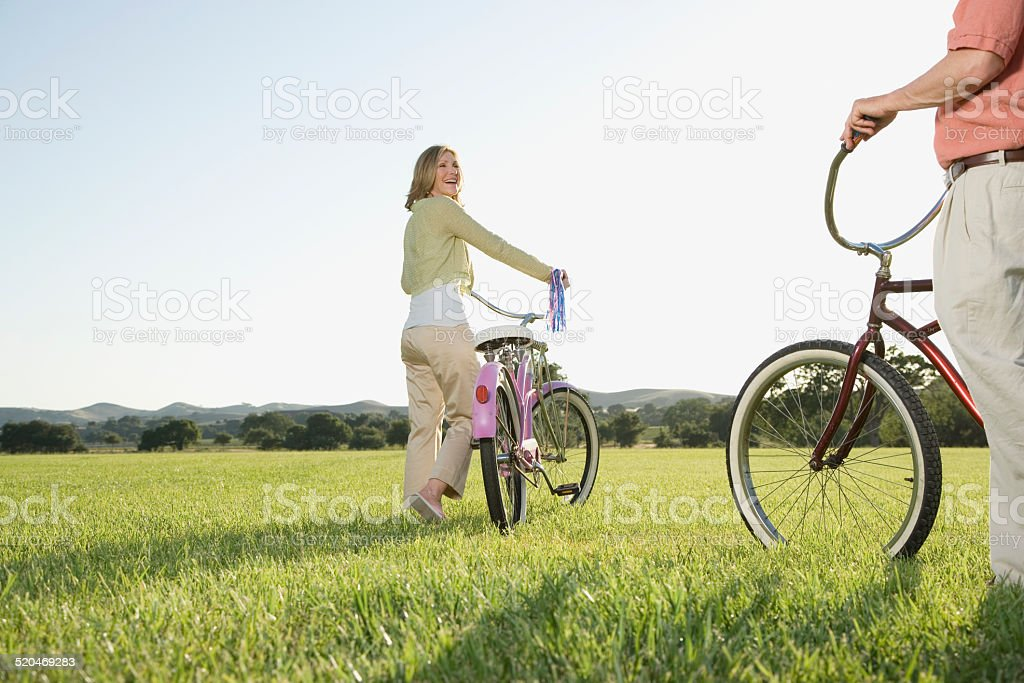 Mature couple on meadow with bicycles stock photo