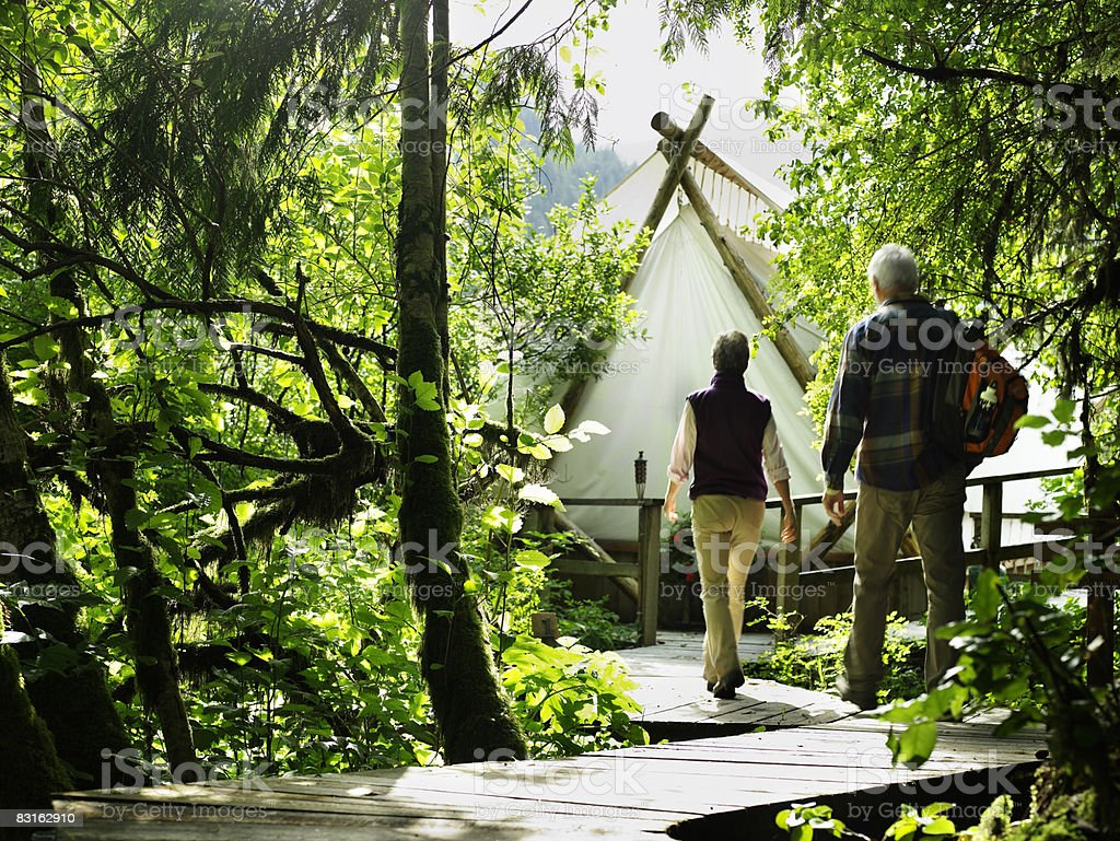 Mature couple on pathway outside tent. royaltyfri bildbanksbilder