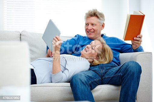 638771390istockphoto Mature couple on sofa with book and digital tablet 476032950
