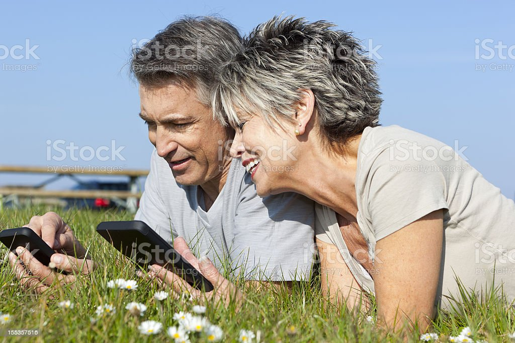 mature couple on their digital tablets royalty-free stock photo