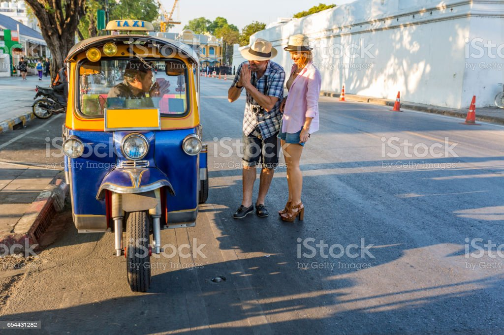 Mature Couple on Vacation Respectfully Paying Tuktuk Transport Driver in Thailand stock photo