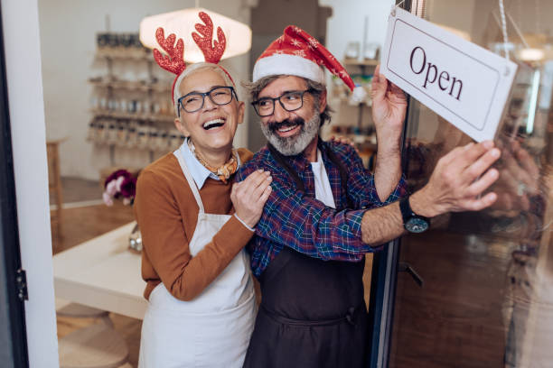 Mature couple opening their shop and celebrating Christmas stock photo