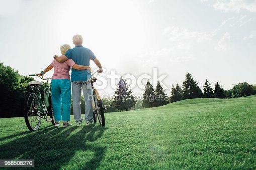 Senior couple with their bicycles standing and hugging, rear view. Active rest of the elderly people