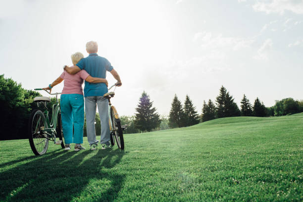 açık havada bisiklet ile olgun çift - sağlıklı yaşlılar stok fotoğraflar ve resimler