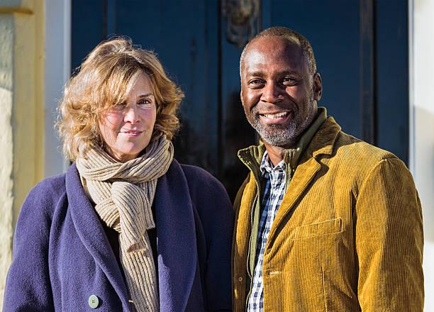 mature couple outside front door - 50 59 jaar stockfoto's en -beelden