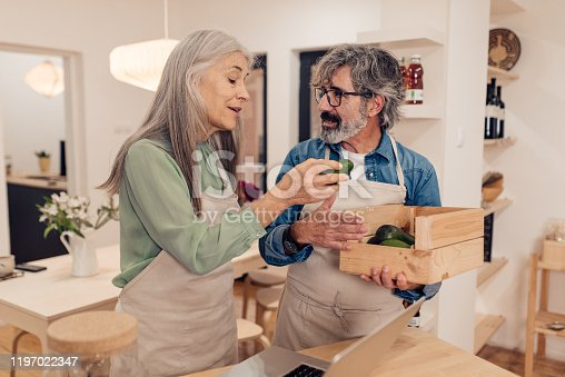 Mature couple arranging groceries in their healthy food store.