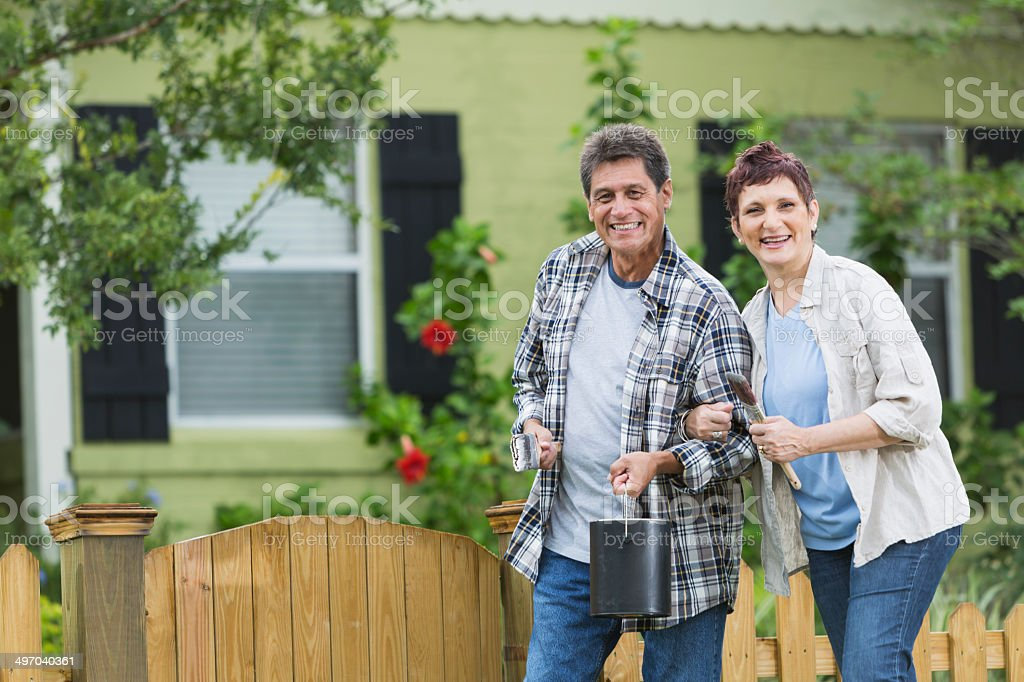 Mature couple painting fence stock photo