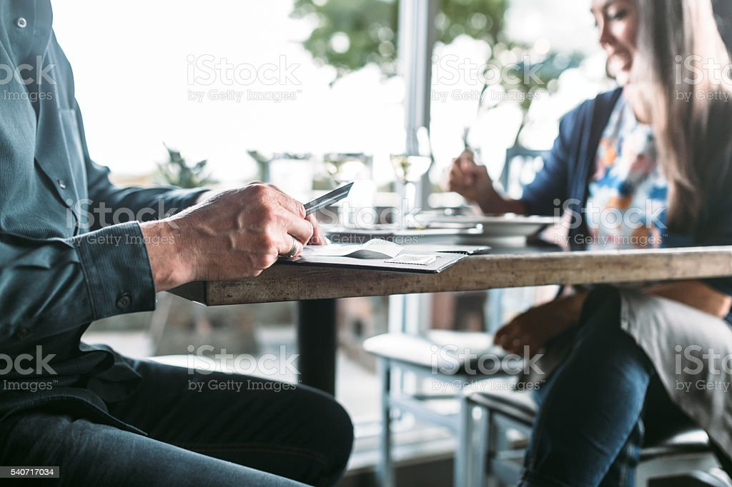 Mature Couple Paying For Dinner stock photo