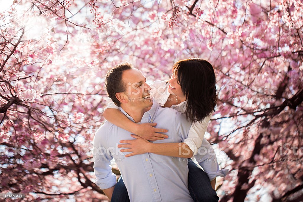 Mature couple piggyback riding in park royalty-free stock photo