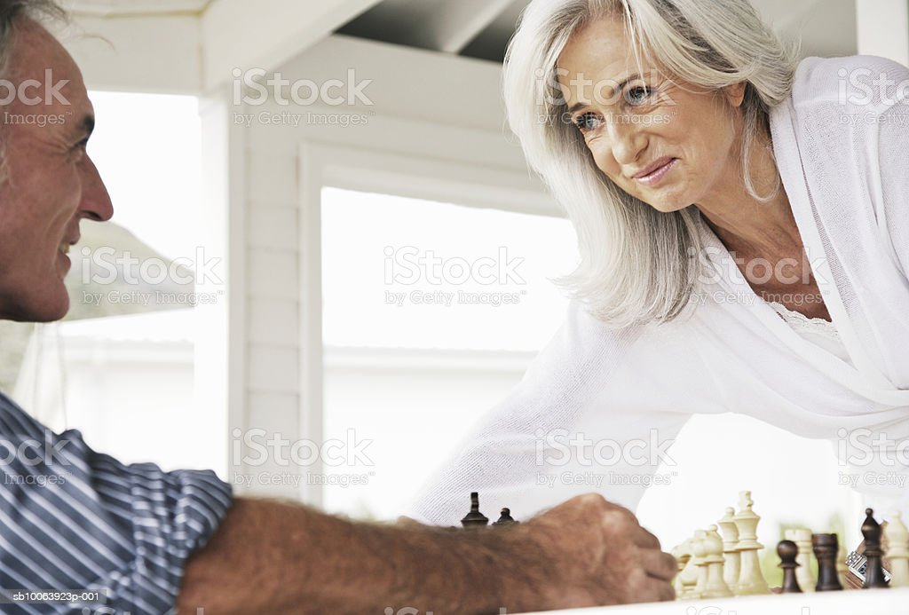 Mature couple playing chess, smiling foto de stock libre de derechos