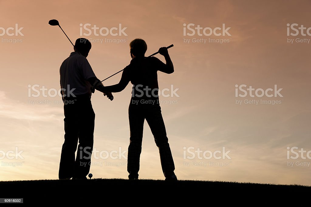Mature couple playing Golf at sunset royalty-free stock photo