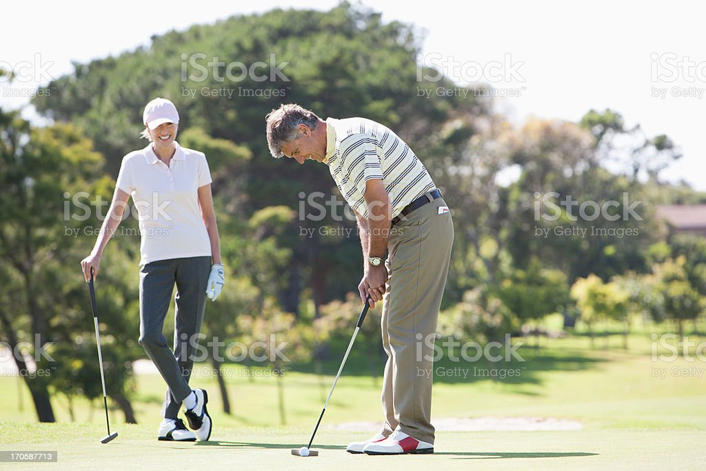 Mature couple playing golf together stock photo