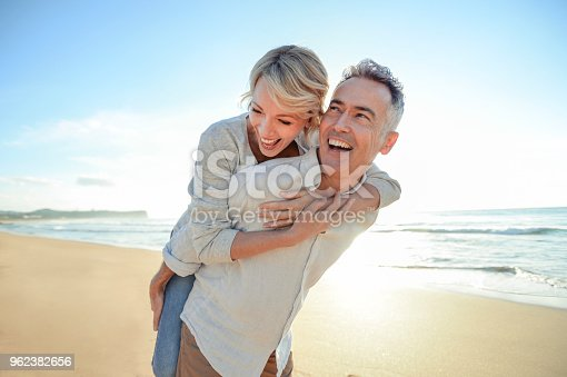 Mature couple playing on the beach at sunset or sunrise. They are having fun, laughing and smiling. The man has grey hair. He is giving his wife a piggyback. Ocean in the background. Back lit with lens flare.